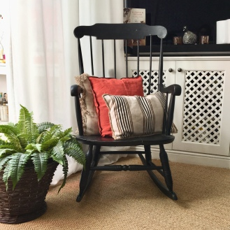 This old american rocking chair repainted in black gives the room both a modern and vintage touch.