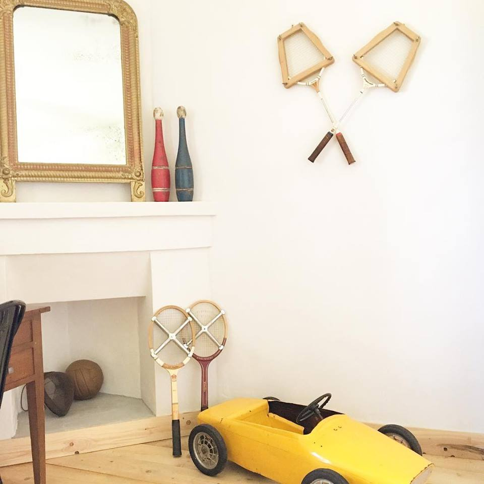 Going for the vintage look in a boy's room can be really charming. I decorated this one with vintage sports equipment and a lovely yellow old kid's car.